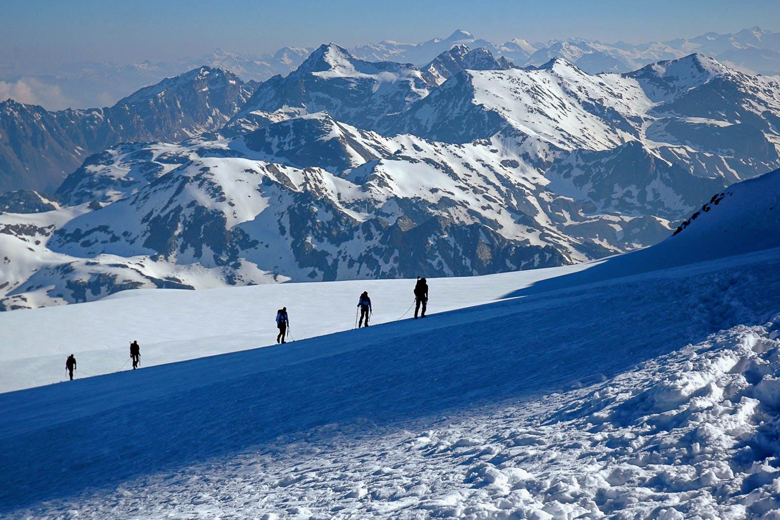 Cordate di alpinisti risalgono, di primo mattino, le affilate creste del monte Castore, 4228 m.