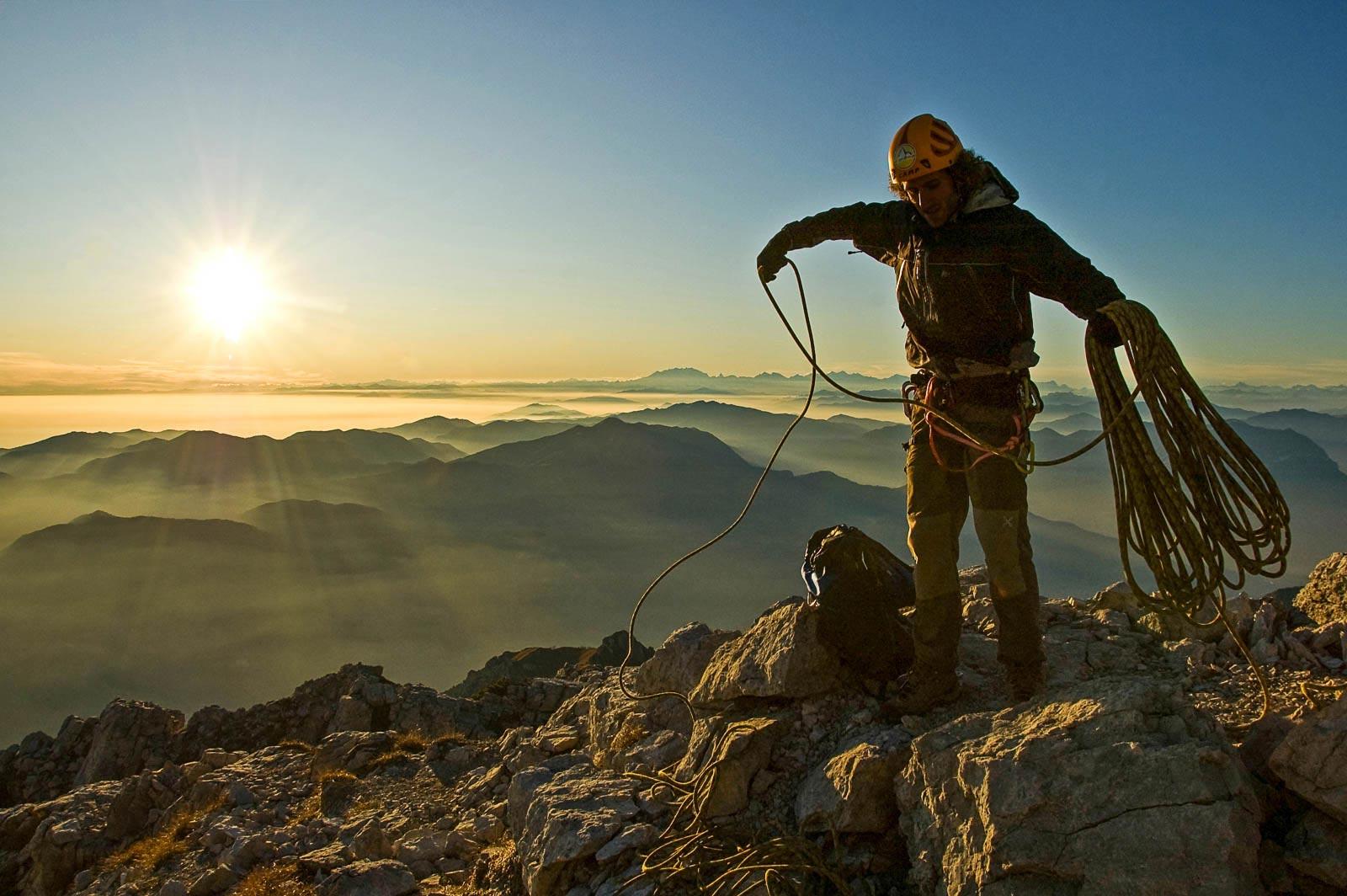Un alpinista riordina la corda al termine della risalita della cresta Segantini, Grigna Meridionale.