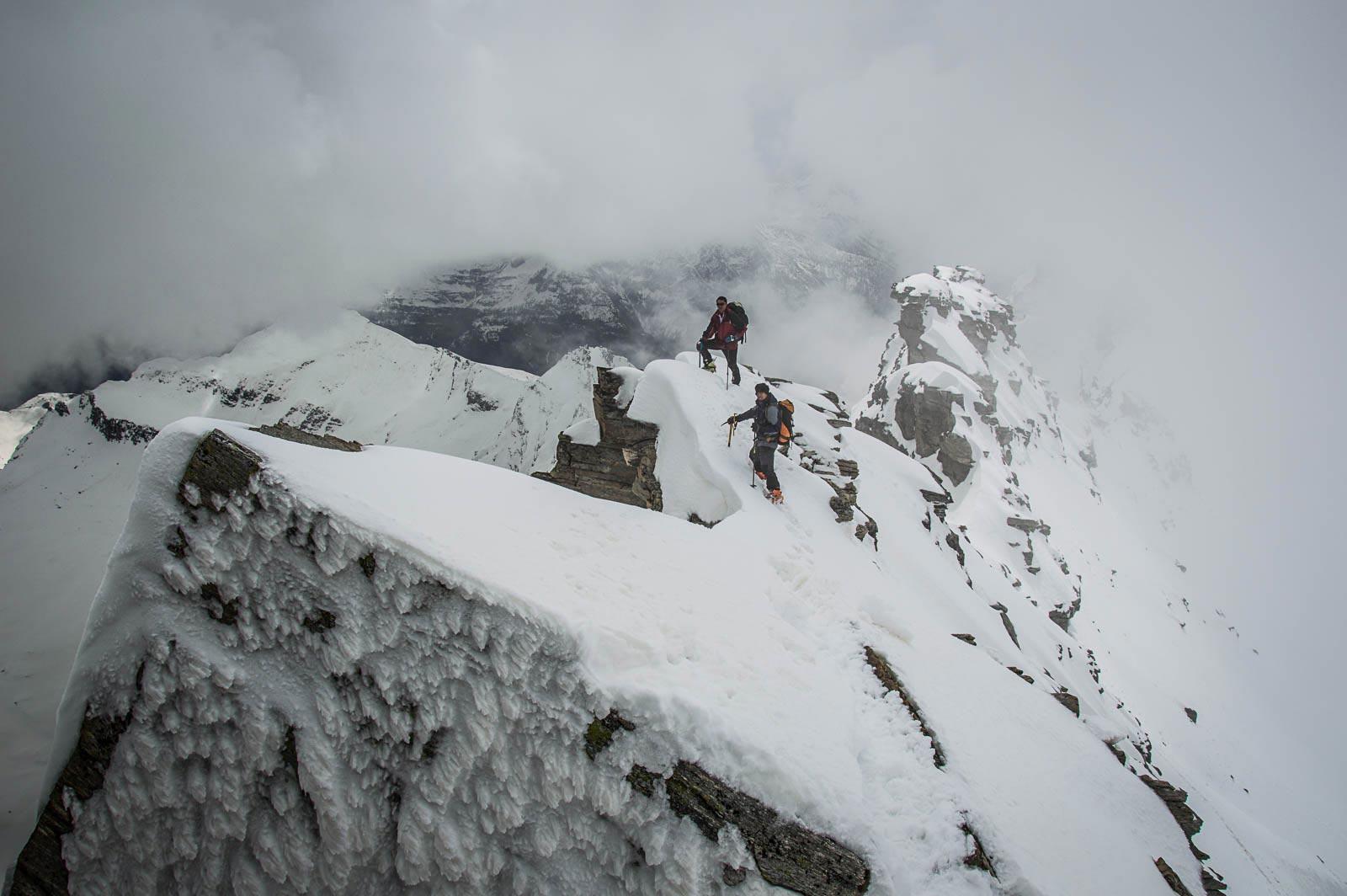 Due alpinisti risalgono la cresta sud del monte Leone, classica scialpinistica primaverile al passo del Sempione.