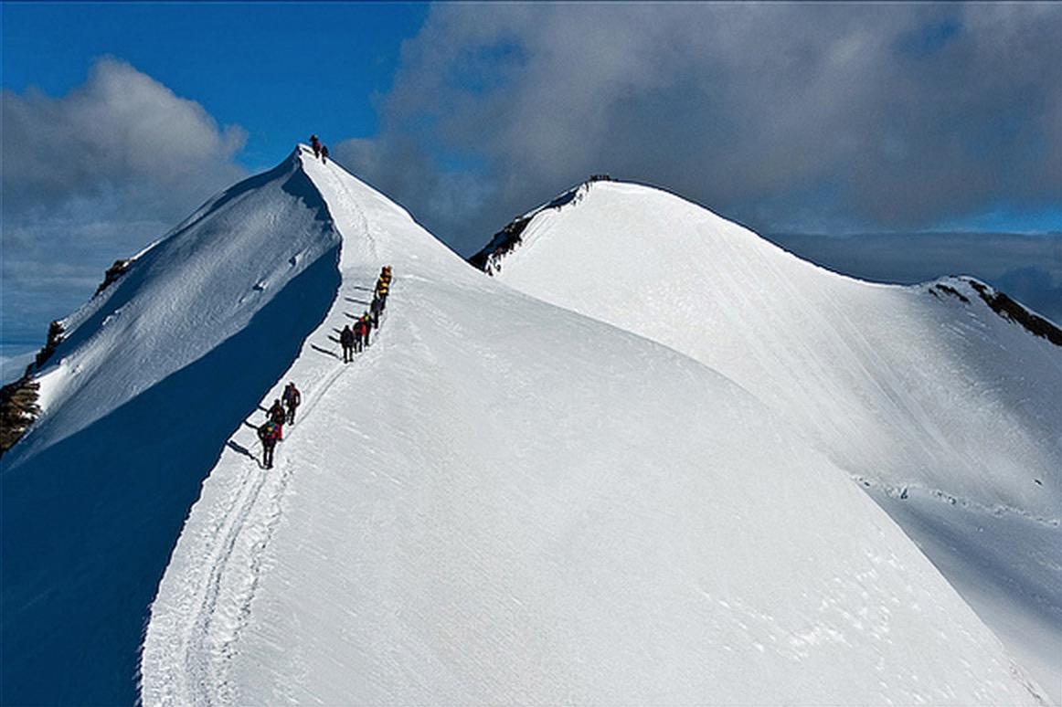 Cordate di alpinisti risalgono la ``schiena di mulo`` sulla via normale al Gran Paradiso, 4061 m.